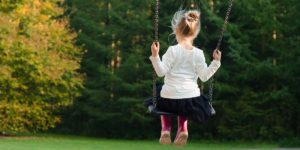 Introverted child alone on a swing